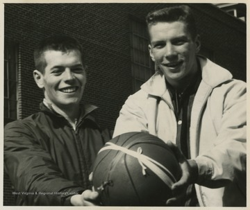 Stover and Green pose with the game ball after securing the state championship victory.Jerry West led the East Bank High School basketball team to its first ever West Virginia state championship title. He was named All-State from 1953–56, then All-American in 1956 when he was West Virginia Player of the Year, becoming the state's first high-school player to score more than 900 points in a season.West was born in Cheylan, W. Va. in 1938. After high school, he went on to play basketball for West Virginia University and then rose to fame as a player for the Los Angeles Lakers of the NBA before becoming a basketball coach and manager.