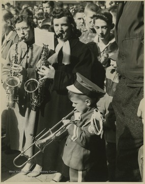 Band members play to celebrate the East Bank High School basketball team winning its first ever state championship title. Young Clinton Jeffreys, mascot for the East Bank High School band, blows a horn to celebrate the homecoming of the State Basktball Champions.