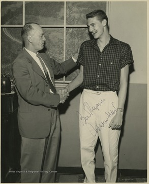Jerry West, right, shakes hands with Coach Williams, left.West led the East Bank High School basketball team to its first ever state championship victory as its starting small forward. He was named All-State from 1953–56, then All-American in 1956 when he was West Virginia Player of the Year, becoming the state's first high-school player to score more than 900 points in a season.West was born in Cheylan, W. Va. in 1938. After high school, he went on to play basketball for West Virginia University and then rose to fame as a player for the Los Angeles Lakers of the NBA before becoming a basketball coach and manager.