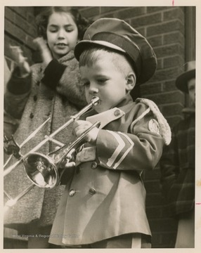 Clinton Jeffreys, mascot for the East Bank High School band, blows a horn to celebrate the homecoming of the State Basktball Champion, East Bank High School, as Susie Williams, age 8, cheers behind him.
