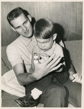 Jerry West sits with his son after he broke his thumb while playing with the Lakers.  West's broken thumb prevented him from playing several games that year.